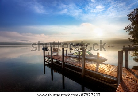 Sunrise through the clouds and mist over a calm New Hampshire lake - stock photo