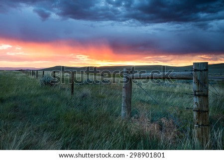Sunrise with a fence in the foreground - stock photo