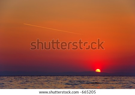 Sunrise with a plane flying on the sky - stock photo