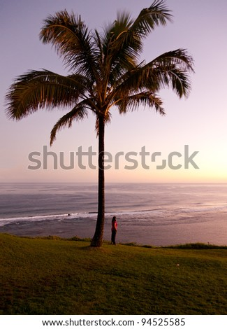 Sunrise with girl by palm tree and looking off into the distance