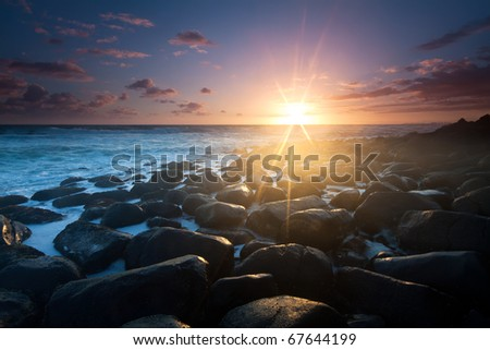 sunrise with interesting full of rocks foreground and nice color clouds in background - stock photo