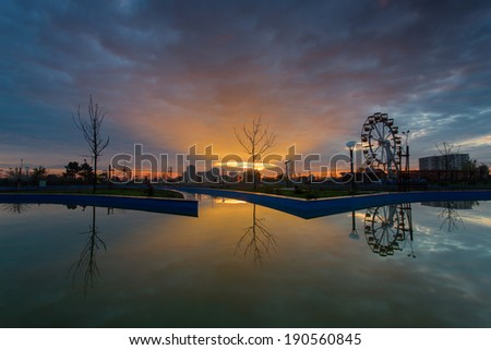 Sunrise with tree with reflection over a lake - stock photo