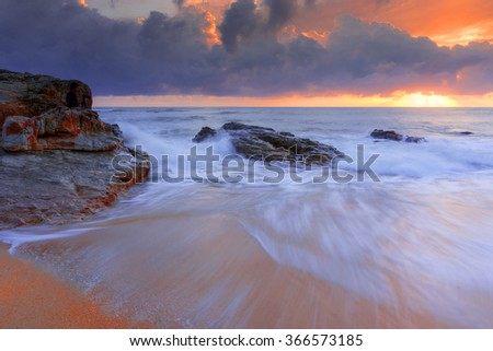 Sunrise with wave at Kemasek Beach taken with Slow Shutter. Soft Focus Motion Blur due to Slow Shutter Speed. Copy Space Area - stock photo