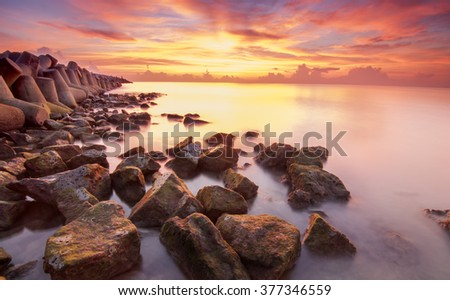 Sunrise with wave at Kemasin Beach taken with Slow Shutter. Soft Focus Motion Blur due to Slow Shutter Speed. Copy Space Area - stock photo