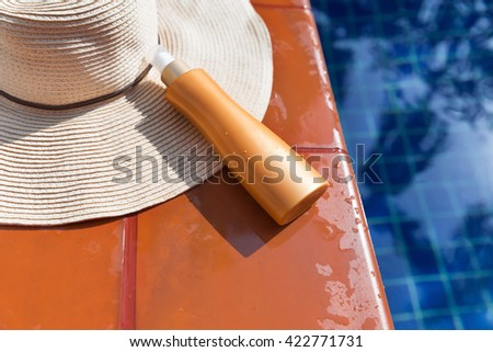 Sunscreen cream with straw hat near swimming pool - summer holiday concept - stock photo