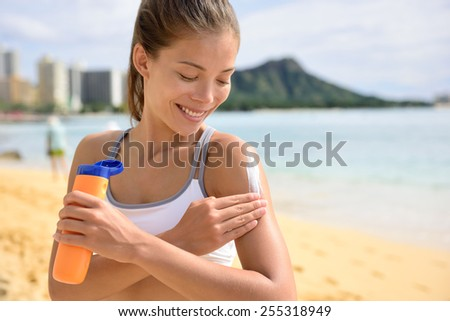 Sunscreen fitness woman applying suntan lotion. Sporty Beautiful happy asian woman with suntan cream applying sun protection before fitness running on beach during summer. Waikiki, Oahu, Hawaii.  - stock photo