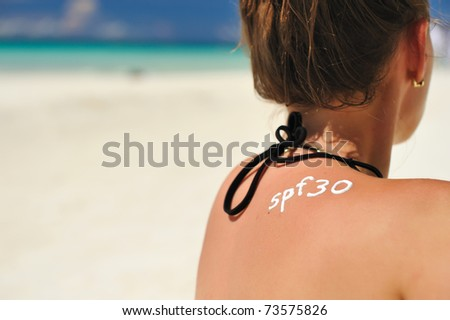 Sunscreen lotion over tan woman skin made as SPF 30 word - stock photo