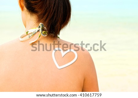Sunscreen lotion over woman skin, Sunbathing. Back view. Close up. - stock photo