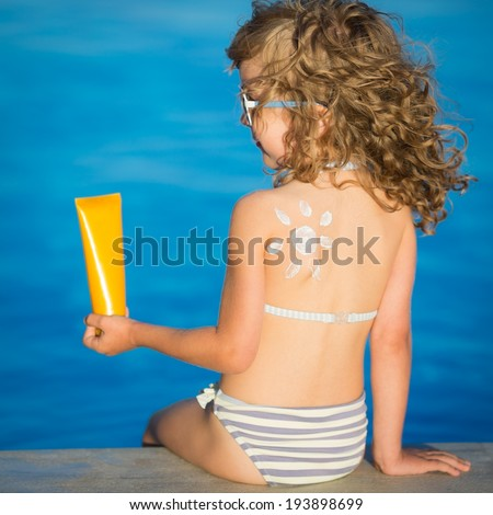 Sunscreen lotion sun drawing on children back. Summer vacation concept - stock photo