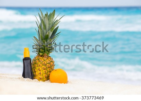 Sunscreen protection cream, pineapple and orange fruits on sand against turquoise caribbean sea water. Tropical summer vacation concept - stock photo