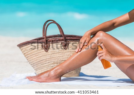 Sunscreen suntan lotion spray bottle woman spraying tanning oil on her leg from bottle. Lady is massaging sunscreen lotion while sunbathing at beach. Unrecognizable model closeup on summer vacation. - stock photo