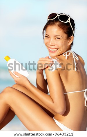 Sunscreen woman. Girl putting sun block on beach holding white sun tan lotion bottle. Beautiful young woman enjoying sunshine on summer vacation. Mixed race Asian / Caucasian female bikini model - stock photo