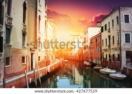 Sunset above the narrow canal in Venice, Italy.  - stock photo