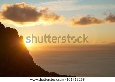 Sunset above the sea with red sky, sun, clouds and mountain