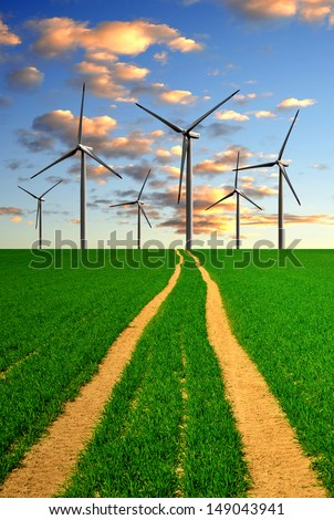 sunset above the spring field with wind turbines