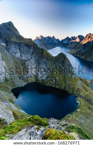 Sunset aerial panoramic view on stunning mountains and village of Reine in Lofoten islands, Norway, from Reinebringen ridge - stock photo