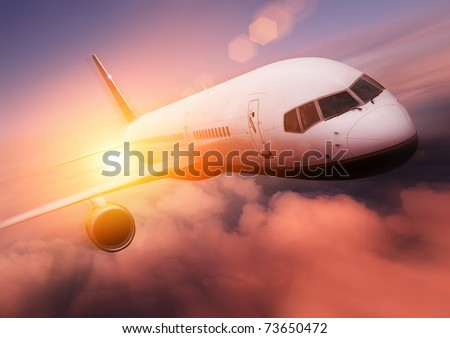 Sunset Airplane Travel. Airliner against the setting sun. - stock photo