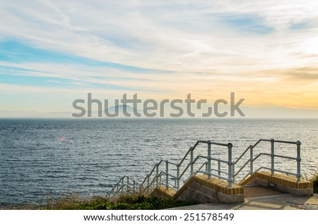 Sunset and a stairs to the sea, view of a Gibraltar's shore with Africa in a distance