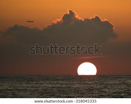 Sunset and airplane. - stock photo