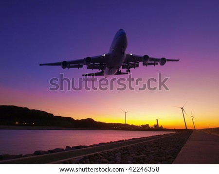 Sunset and airplane fly over river - stock photo