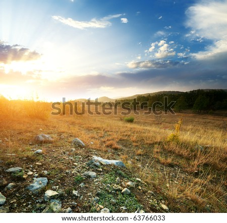 Sunset and big green meadow. Composition of nature. - stock photo