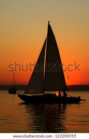 Sunset and boat with people - stock photo