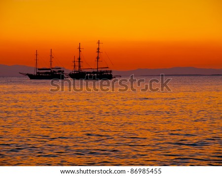 Sunset and boats on the sea - stock photo