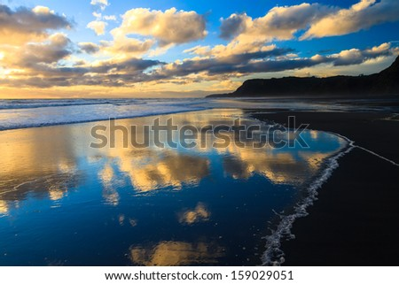 Sunset and Clouds Reflection in the Sea at Karekare Beach, New Zealand - stock photo