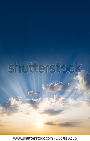 Sunset and clouds with sunbeams - stock photo
