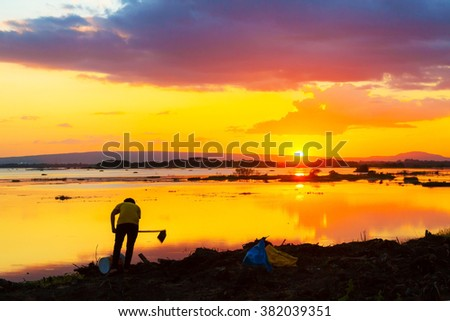 Sunset and farmer on river in countryside, Sakon Nakhon Thailand - stock photo