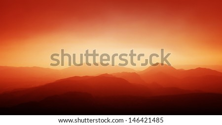 Sunset and mountain silhouette. - stock photo