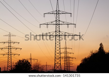Sunset and power cables running diagonally through the picture - stock photo