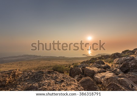 Sunset and ray path at the top of Antelope Island with rocks at the foreground located near Salt Lake City, Utah.  - stock photo