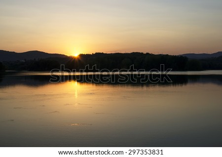 sunset and reflections in the lake - stock photo
