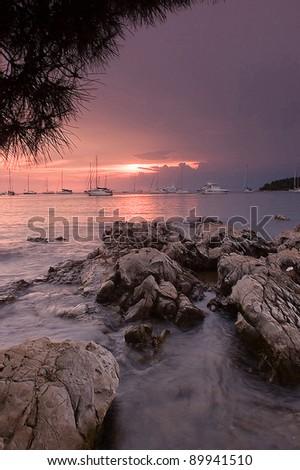 Sunset and rocks at a bay in Rovinj, Croatia - stock photo