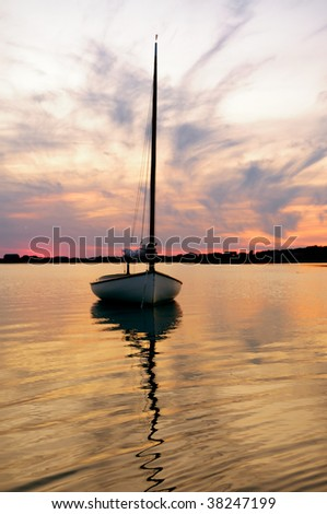 Sunset and sailboat in Martha's Vineyard, Massachusetts. - stock photo