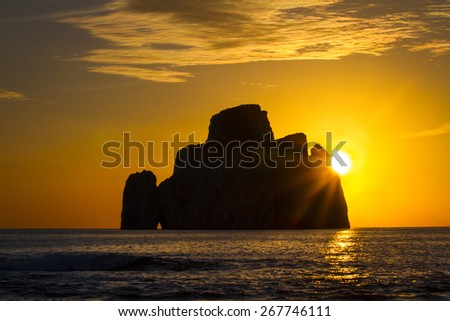 Sunset and seascape with cloudy sky and sun back the island. Sardinia - stock photo