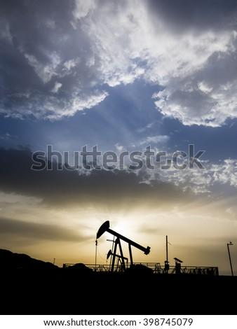 Sunset and silhouette of crude oil pump in oil field. - stock photo