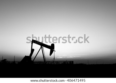 Sunset and silhouette of crude oil pump in oilfield -black and white - stock photo