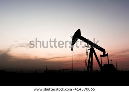 Sunset and silhouette of crude oil pump in the oilfield - stock photo