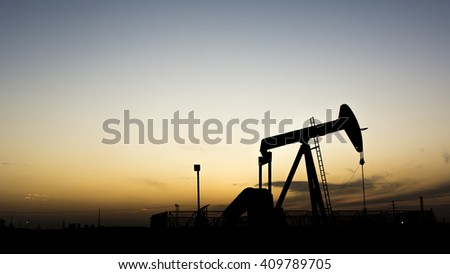 Sunset and silhouette of crude oil pumping unit in oilfield
