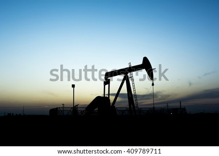 Sunset and silhouette of crude oil pumping unit in oilfield  - stock photo