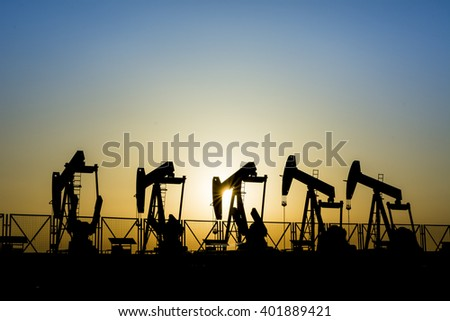 Sunset and silhouette of crude oil pumps in oil field.