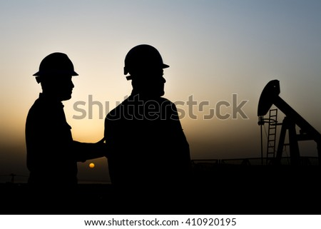 Sunset and silhouette of oilfield worker in the oilfield - Blur crude oil pump background  - stock photo