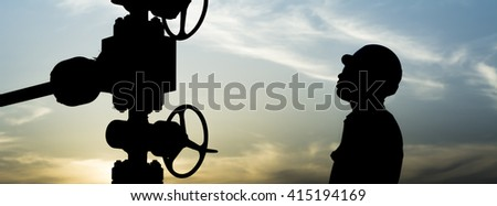 Sunset and silhouette of oilfield worker monitoring wellhead in oilfield