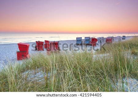sunset at a beach of Baltic sea, beach chairs Standing in the White sand