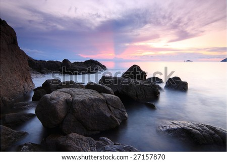 Sunset at a rocky beach in a tropical island. Long exposure.