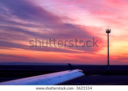 Sunset at airfield (cloudscape and aircraft wing). - stock photo