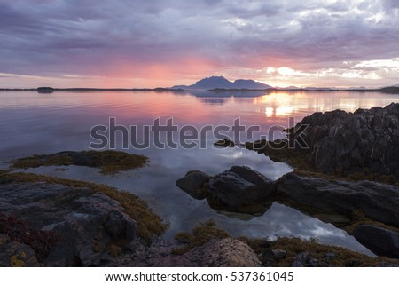 Sunset at beautiful quiet evening at seaside. Coastal rocks at Helgeland archipelago, Norway.