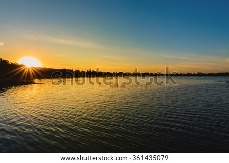 sunset at coast of the lake - stock photo